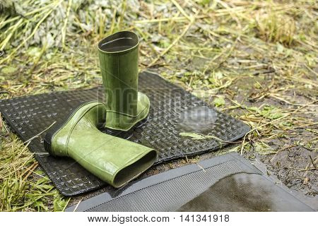 Children green boots left in the rainy weather outdoor one is filled with by rainwater on a background green grass