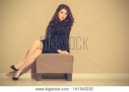 Pretty woman sitting on stool in light room