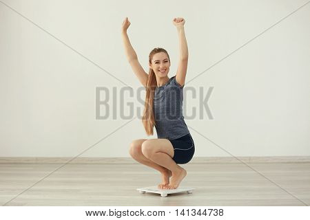 Beautiful young woman weigh on floor scales