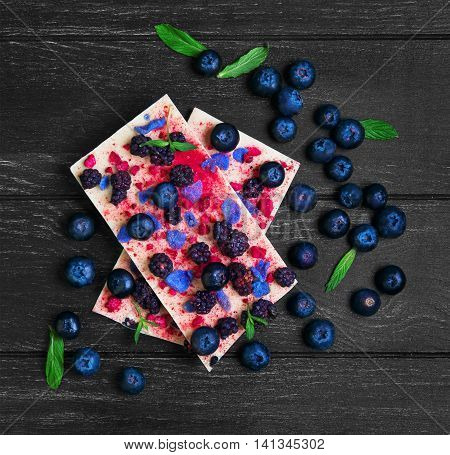 Chocolate bars White blackberries blueberries blueberry raspberry candied violet petals mint leaves candy heart on dark black background wooden surface empty place for text top view