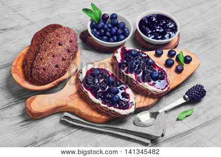 Sweet berry crostini sandwiches with blackberry jam and berries blueberries whole grain bread for sandwiches sandwiches board spoon mint leaves on bright white background wooden