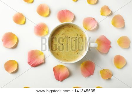 Pink rose petals with cup of coffee on white background
