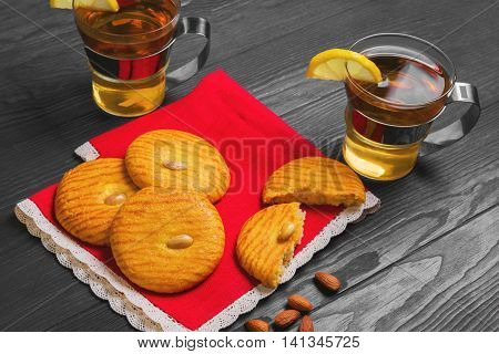 Italian almonds cookies amaretti entire three pieces on red lacy napkin amaretti cookies broken down one half nuts almonds two cups of black tea with lemon slices on dark brown wooden background