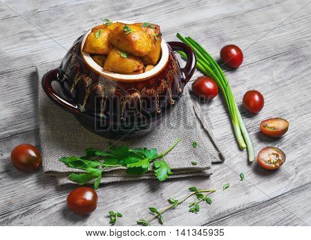 Baked potatoes in the oven in a special ceramic pot for roasting potatoes chives thyme parsley burlap cloth on a bright white background wooden