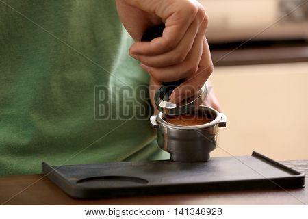 Barista pressing ground coffee with tamper in portafilter