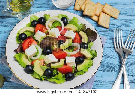Vegetarian meal salad of avocado olives onions cherry tomatoes feta cheese lettuce avocado oil salt bread crackers on napkin blue wooden background