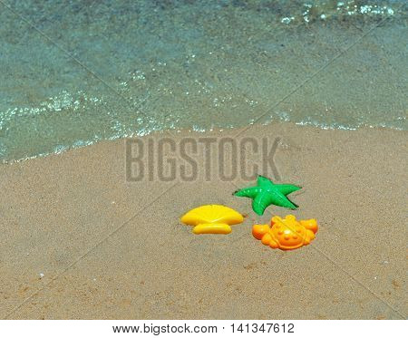Three children's plastic forms for playing with sand green starfish shell yellow orange crab sand Beach sea