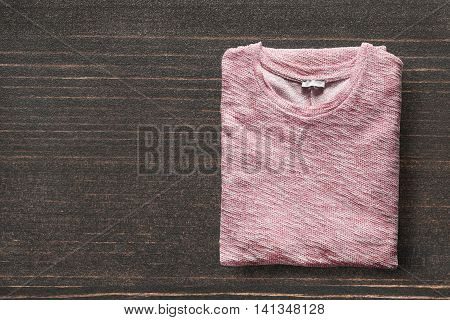 Folded pink pullover on dark wooden background