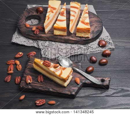 Cakes Cheesecake caramel nut slices spoon wooden cutting boards burlap lace chestnuts almonds pecans dark brown wooden background