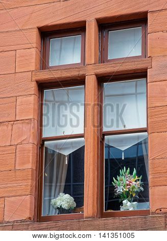 Wooden window with flower pots in the Old City of Glasgow. Glasgow is the city in the Lowlands in Scotland in the United Kingdom.