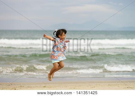 Small Girl Jumping With Happiness At China Beach In Danang