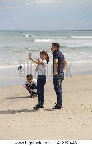 Young People Using Selfie Stick At China Beach Danang