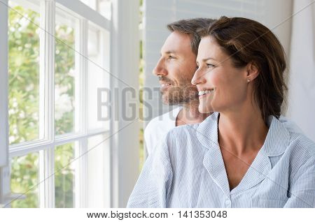 Cheerful young couple looking outside window. Portrait of smiling couple thinking about the future. Happy cheerful couple relaxing at home.