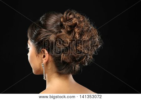 Young beautiful woman with nice hairdo on black background