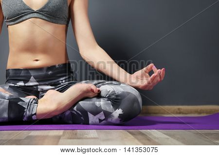 Girl practicing advanced yoga on grey wall background