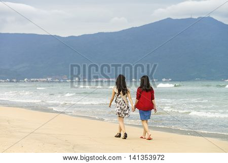 Young Girls Passing By On China Beach Of Danang