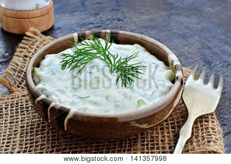 Tzatziki Greek yogurt cucumber sauce in rustic stoneware bowl over wooden table.
