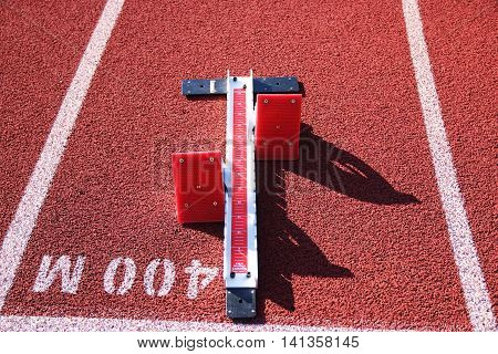 A set of red starting blocks set up at the 400m start on a red and white track