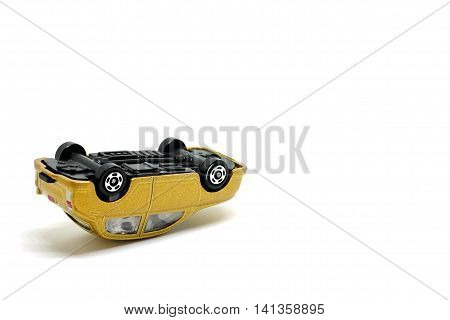 Golden toy cars overturned on a white background