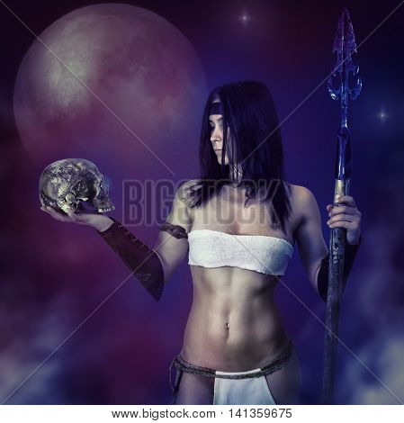 Beautiful girl in image of the ancient barbarian warrior on a mystical background with a skull in his hand.