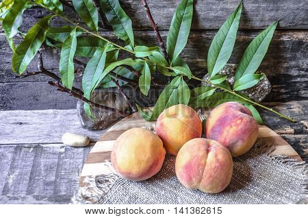 The branch with leaves and peaches on cutting board on background old burnt boards