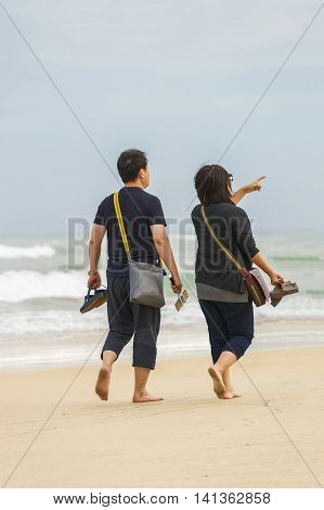 Danang Vietnam - February 20 2016: Young couple passing by at the China Beach in Danang in Vietnam. No face