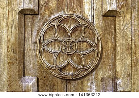 Cut out on church wooden door the sun with a cross,symbol of eternity