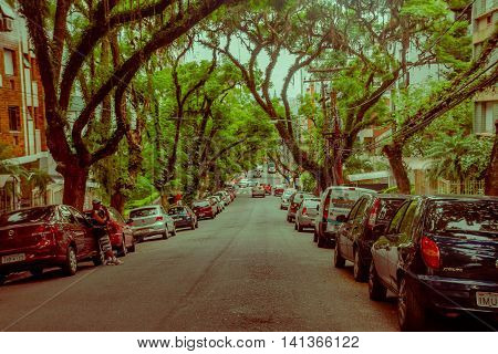 PORTO ALEGRE, BRAZIL - MAY 06, 2016: nice street with big trees in the sidewalks, lot of cars parked outside the buildings.