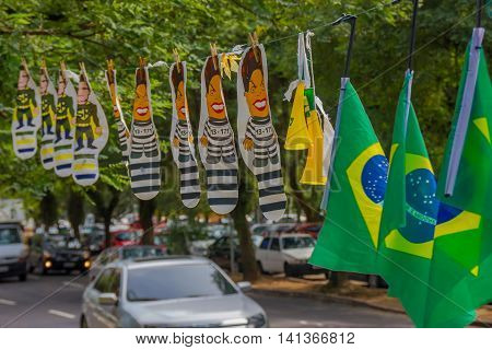 PORTO ALEGRE, BRAZIL - MAY 06, 2016:brazilian flags hanging next to dilma rousseff and sergio moro cartoons in the street.
