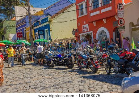 CURITIBA , BRAZIL - MAY 12, 2016: unidentified people lokking to some motorcycles parked in the street close to the square where the marked place is located.