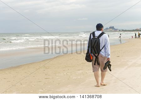 Young man passing by at the China Beach in Danang in Vietnam. No face