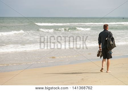 Danang, Vietnam - February 20, 2016: Young man passing by at the China Beach Danang in Vietnam. No face