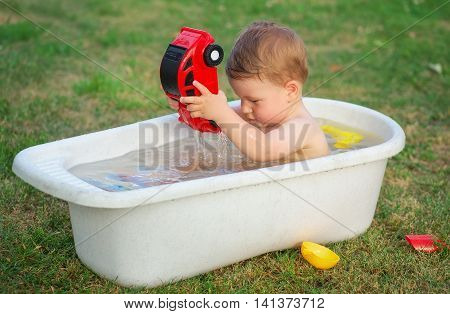 A small baby bathed in the bath and playing with toy car.