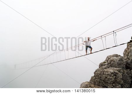 Man walks on a suspension bridge on the cliffs in the fog.