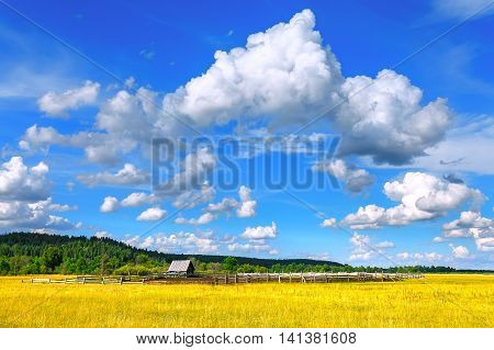 Landscape with small wooden house blue sky and clouds. Russia.