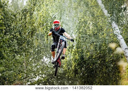 athlete extreme jump on a bike in forest during competition downhill