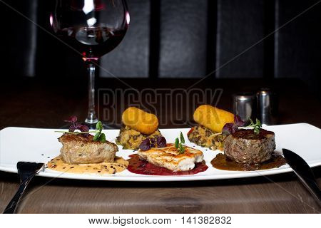 variety of meats served with a glass of red wine, horizontal, dark background