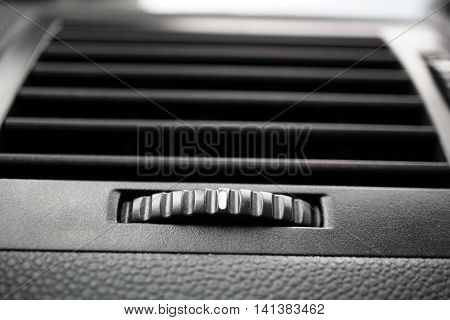 Modern automotive car air conditioning (car ventilation vent) with gradient rounded control wheel in black color