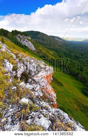 Mountain valley with green trees and grass with the top of the mountain. Under a blue sky with clouds. Russia.