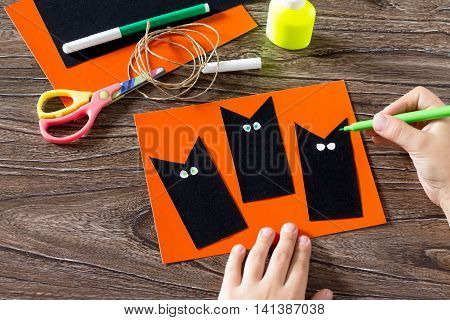 The Child Create A Greeting Card Halloween Black Cat Out Of Paper, Drawing Paper Parts. Glue, Scisso
