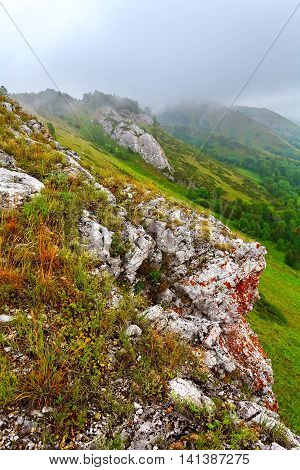 Mountain landscape with green trees and grass. Shrouded in fog. Russia.