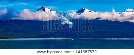 Tracy Arm Fjord AK USA - May 27 2016: Panorama of one of the many mountain peaks islands and forest areas as seen while cruising the Tracy Arm Fjord in Alaska. Panorama of glacier peaks low clouds and still waters in the Tongass National forest.