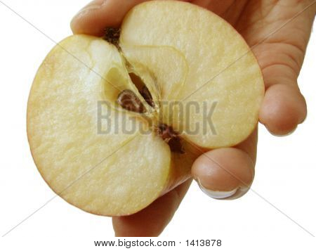A Female Hand Holding The Part Of A Cut Apple