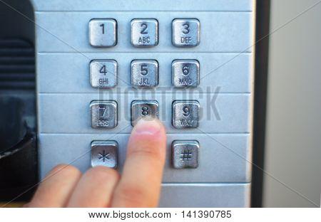 finger pushing telephone button public cabin, metallic buttons