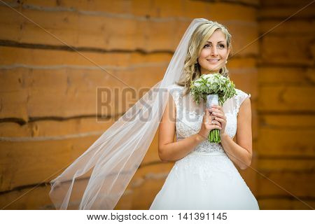 Gorgeous bride on her wedding day  holding her lovely bouquet (color toned image; shallow DOF)