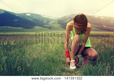 young woman trail runner tying shoelace on trail