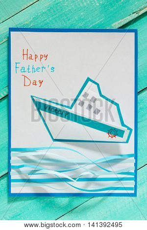 The Child Makes Crafts Out Of Paper Boats. Greeting Card For On Father's Day. Children's Art Project