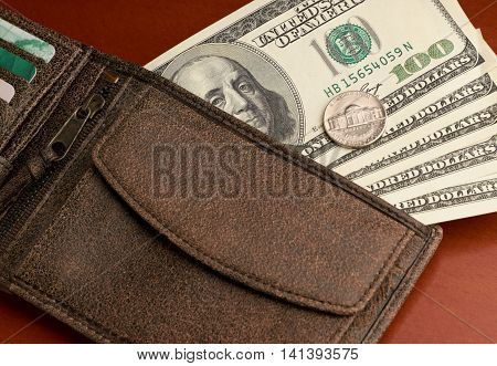 US dollars in a wallet on wooden table