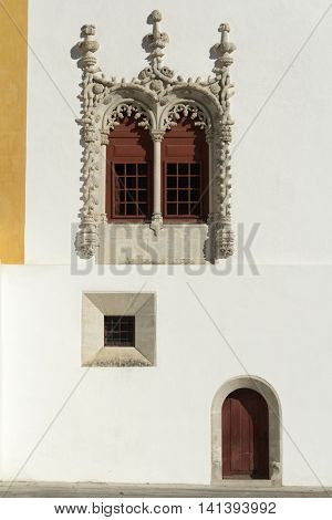 A Manueline window and simple door in the National Palace of Sintra, Portugal.