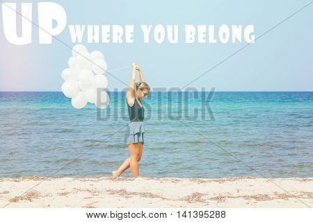 Young woman walking the beach with white ballons